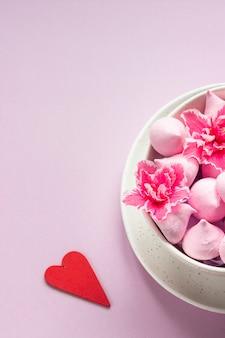 Małe bezy i różowe kwiaty w ceramicznej misce. prezent na walentynki.