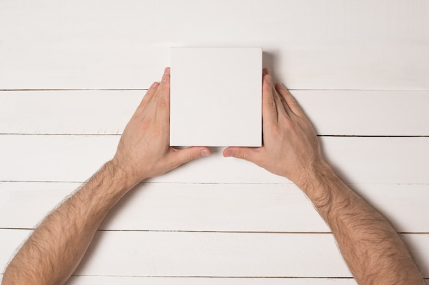 Małe białe kartony w męskich rękach.