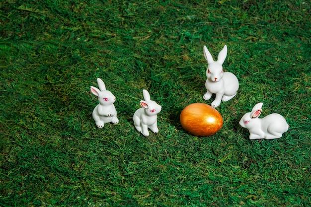 Małe białe króliczki wokół złotego jajka na tle mchu