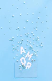 Małe białe kwiaty, jasnoniebieska koperta i napis amor na jasnoniebieskim tle widok z góry