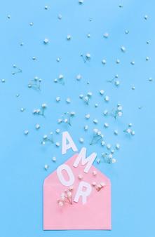 Małe białe kwiaty, różowa koperta i napis amor na jasnoniebieskim tle widok z góry