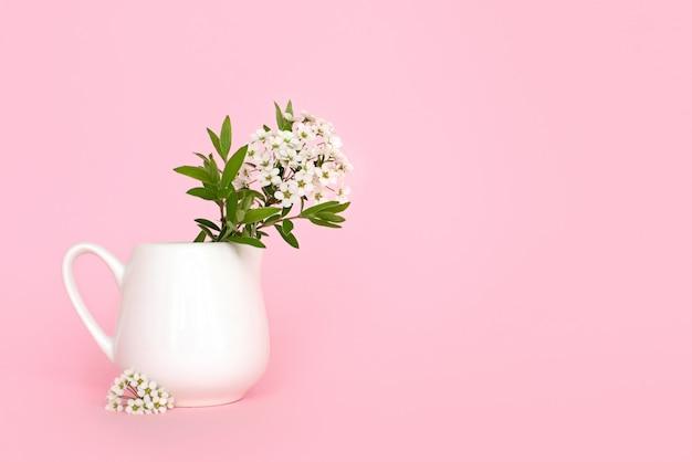 Małe białe kwiaty w wazonie na różowym tle. zdjęcie wysokiej jakości