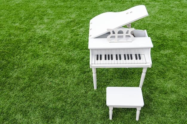 Małe białe pianino dla dzieci na zewnątrz na sztucznej trawie