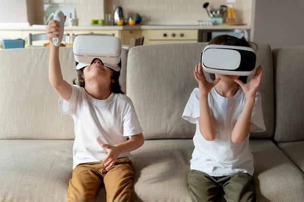 Małe bliźniaki grają w grę w wirtualnej rzeczywistości