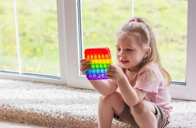 Małe blond dzieci bawią się z nowym trendem sensorycznej zabawki tęczy pop it. zabawka antystresowa dla dzieci i dorosłych. kolorowa zabawka z prostym wgłębieniem. squishy miękkie zabawki bąbelkowe w kolorze tęczy!