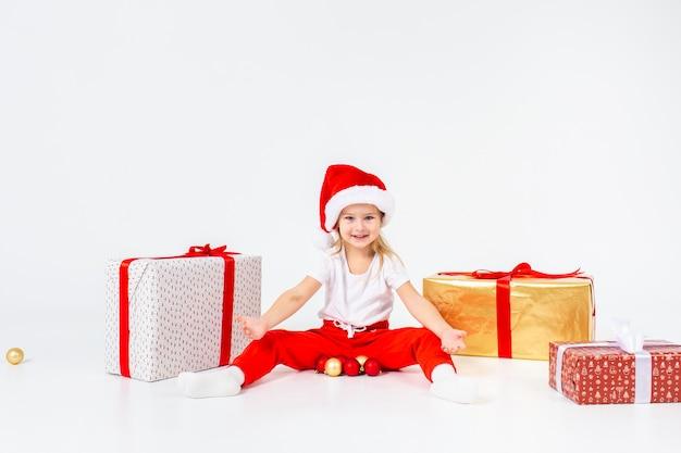 Małe blondynki dzieci w czapce świętego mikołaja siedzą między pudełkami i bawią się bombkami.