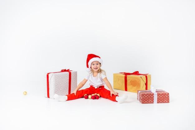Małe blondynki dzieci w czapce świętego mikołaja siedzą między pudełkami i bawią się bombkami