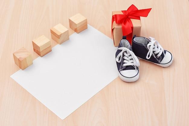 Małe buciki dziecięce z pudełkiem na prezenty na drewnie