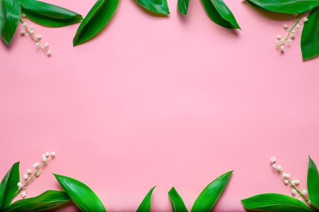 Małe bukiety konwalii i zielonych liści jako kwiecista ramka z płaskimi miejscami do kopiowania