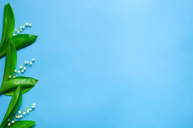 Małe bukiety konwalii jako kwiatowe obramowanie po lewej stronie z miejscem do kopiowania flat lay