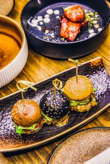 Małe burgery podawane na jednym talerzu jako przystawka