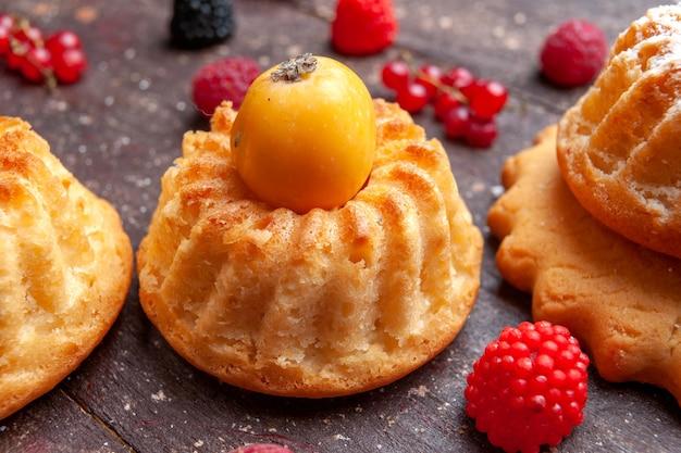 Małe ciasta ze świeżymi owocami na brązowym, owocowym berry bake bake bake