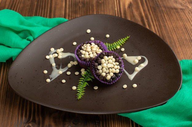 Małe ciasteczka czekoladowe z kawałkami czekolady wewnątrz ciemnego talerza na drewnie
