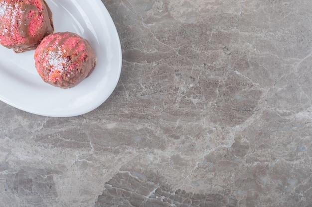 Małe ciasteczka z przekąskami na półmisku na marmurowej powierzchni