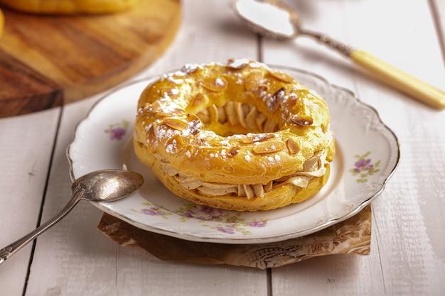Małe ciasto paris brest w starym talerzu na białym drewnianym stole