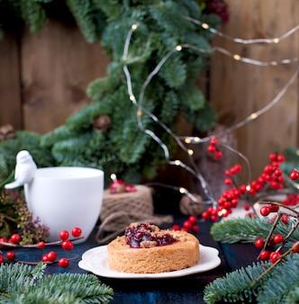 Małe ciasto z dżemem żurawinowym na niebieskiej drewnianej choince