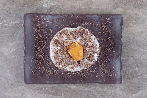 Małe ciasto z posiekaną pomarańczową polewą na talerzu z marmuru