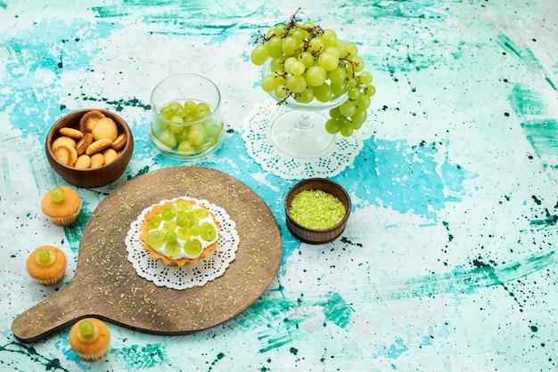 Małe ciasto z pyszną śmietaną i pokrojone i świeże ciasteczka z zielonych winogron na białym tle na niebieski, ciasto słodkie cukier owocowy piec