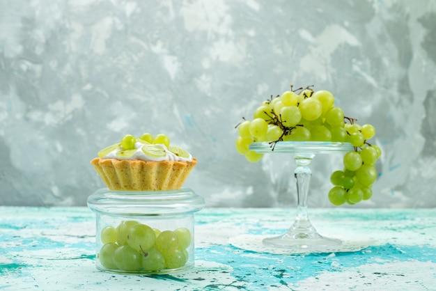 Małe ciasto z pyszną śmietaną i pokrojonymi w plasterki i świeżymi zielonymi winogronami na białym tle na niebieski, ciasto słodkie cukier owocowy piec
