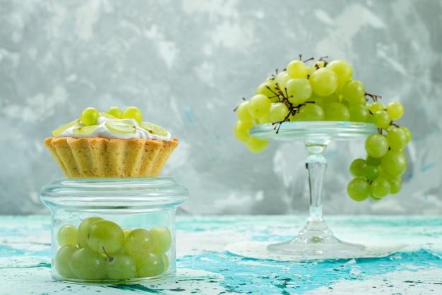 Małe ciasto z pyszną śmietaną i pokrojonymi w plasterki i świeżymi zielonymi winogronami na niebieskim tle, słodkie ciasto owocowe