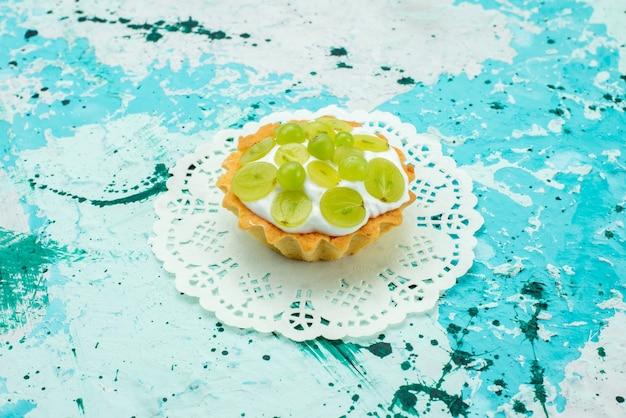 Małe ciasto z pyszną śmietaną i pokrojonymi w plasterki zielonymi winogronami na białym tle, ciasto słodkie cukier owocowy
