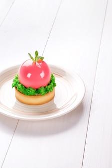 Małe ciasto z różnym nadzieniem na białym talerzu biały drewniany stół