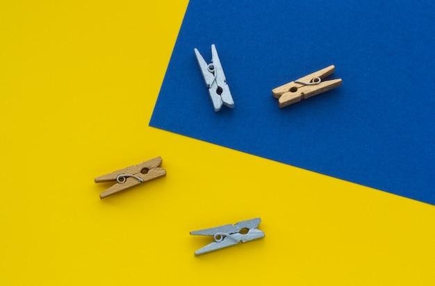 Małe clothespins na żółtym tle niebieskiego