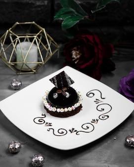 Małe czarne ciasto ozdobione chockolate