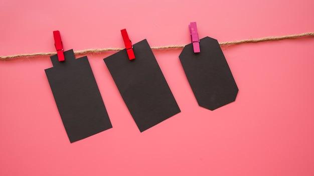 Małe czarne kartki papieru wiszące na nitce