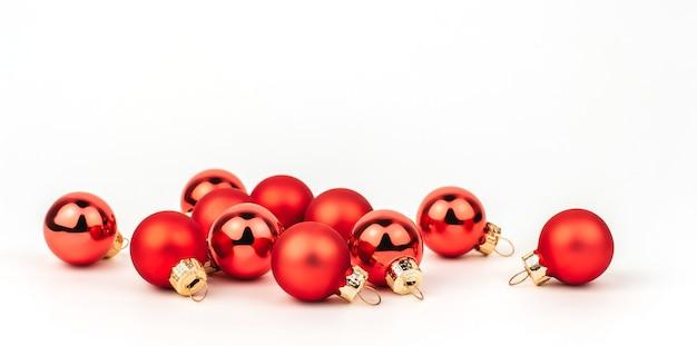 Małe czerwone bombki na białym tle.
