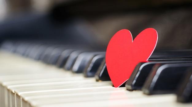 Małe czerwone papierowe serce na klawiszach fortepianu
