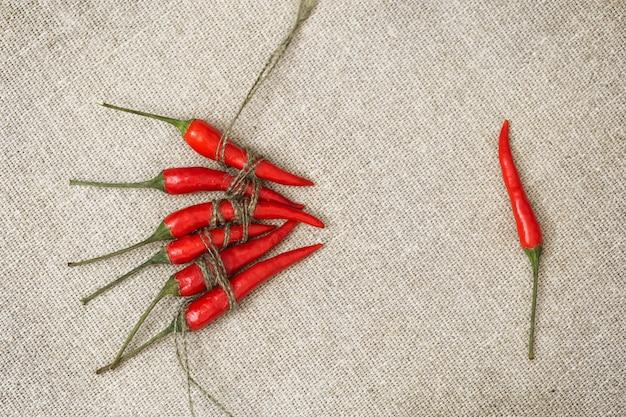 Małe czerwone papryczki chili związane liną w grupie i jeden pieprz