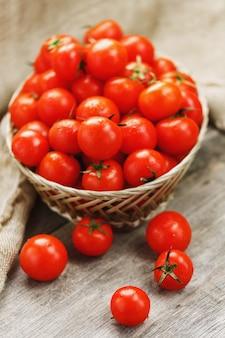 Małe czerwone pomidory w wiklinowym koszu na starym drewnianym stole. dojrzała i soczysta wiśnia