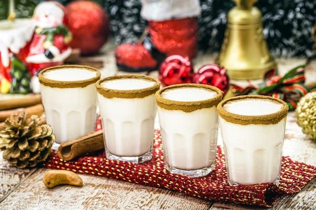 Małe dawki ciepłego świątecznego ajerkoniaku na bazie jajek i likieru rumowego. zwany ajerkoniakiem, momo cola, coquito lub crã¨me de vie