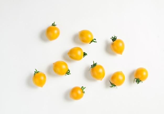 Małe dojrzałe żółte pomidory cherry na białym tle