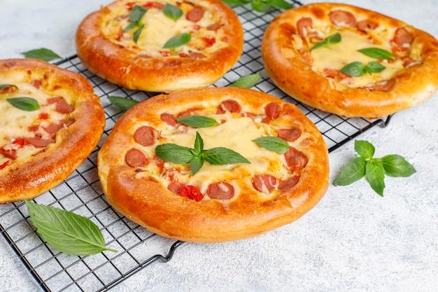 Małe domowe pizze świeże z bazylią.
