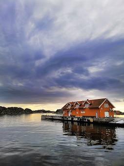 Małe domy na doku pod zachmurzonym niebem