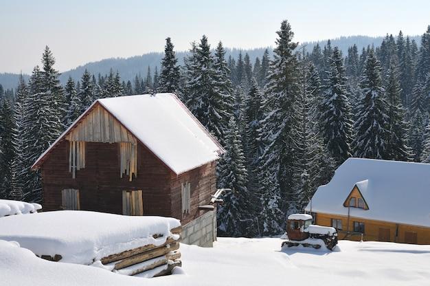 Małe drewniane domki na tle pięknego śnieżnego górskiego lasu