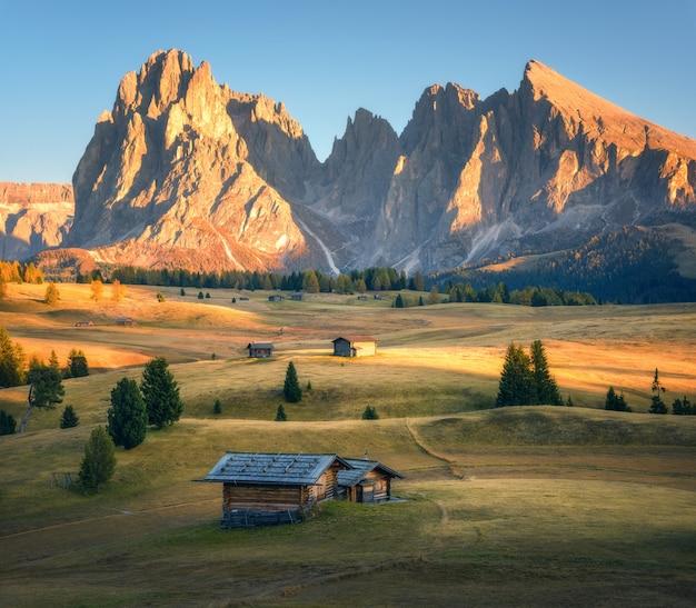 Małe drewniane domy w pięknej górskiej dolinie o zachodzie słońca