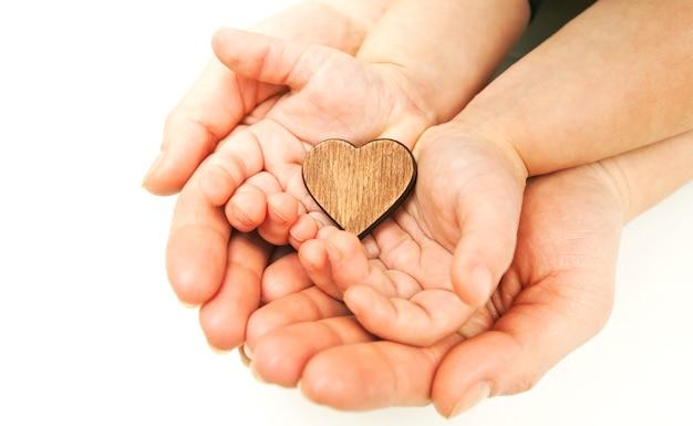 Małe drewniane serduszko w dłoniach kobiety i dziecka