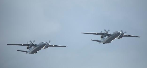 Małe dwa dwusilnikowe śmigłowe wojskowe samoloty rozpoznawcze na tle nieba.