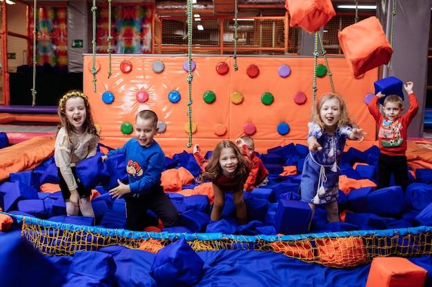 Małe dzieci bawią się i bawią w suchym basenie z kostkami paralon w centrum rozrywki dla dzieci