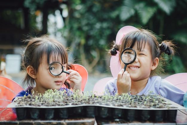 Małe dzieci bawią się i zwiedzają w ogrodzie z kiełkami do sadzenia.