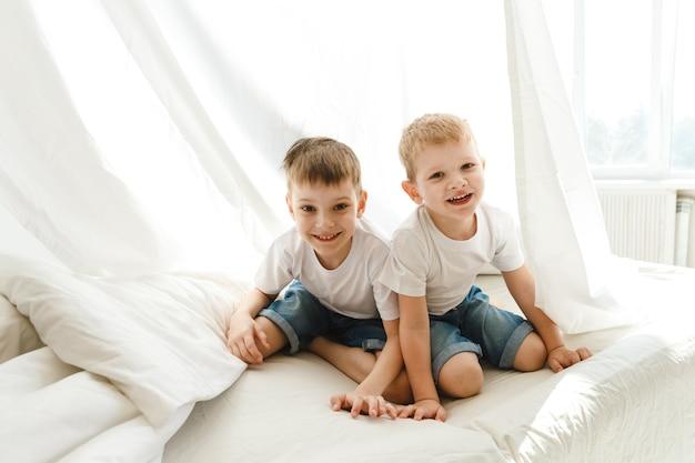 Małe dzieci bawią się na łóżku i w chacie z prześcieradła.