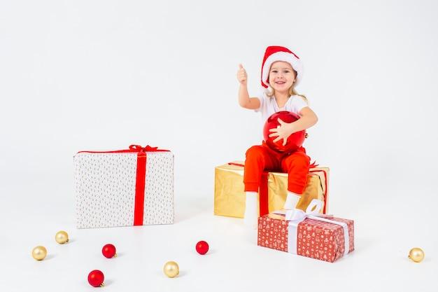 Małe dzieci blondynka w czapce mikołaja siedzi na pudełka i trzyma kciuk do góry. pojedynczo na białym tle. święta, święta, nowy rok, koncepcja x-mas. copyspace.