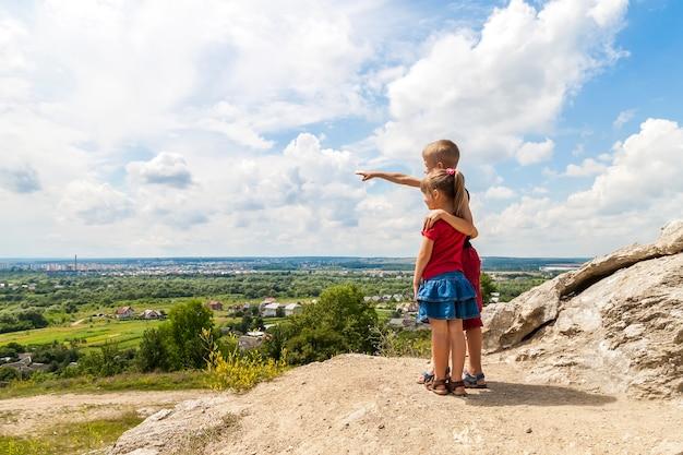 Małe dzieci chłopiec i dziewczynka stojąc na skale góry i patrząc w przyszłość. chłopiec pokazuje z jego ręką