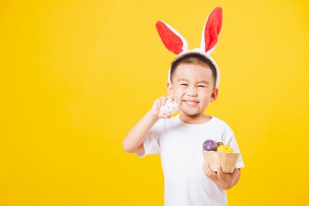 Małe dzieci chłopiec z królików ucho trzyma wielkanocnych jajka w wielkanocnego festiwalu dniu