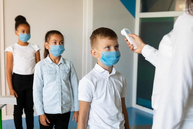 Małe dzieci czekają w kolejce, aż nauczyciel zmierzy im temperaturę