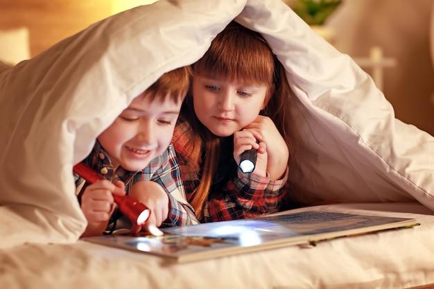 Małe dzieci czytają książkę pod kocem w nocy