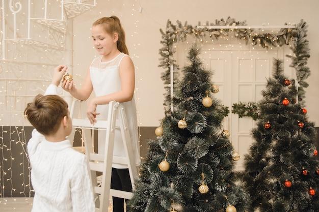 Małe dzieci dekorują choinkę w jasnym wnętrzu. dziewczyna chłopca, siostra brora powiesić zabawki na gałęzi świerka. święta rodzinne